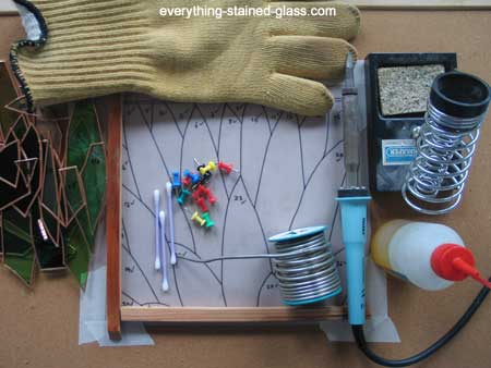A collection of things you need to solder stained glass including soldering iron, solder and flux