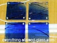 blue stained glass with drilled holes and bolts