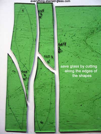 four rough shapes cut from green glass